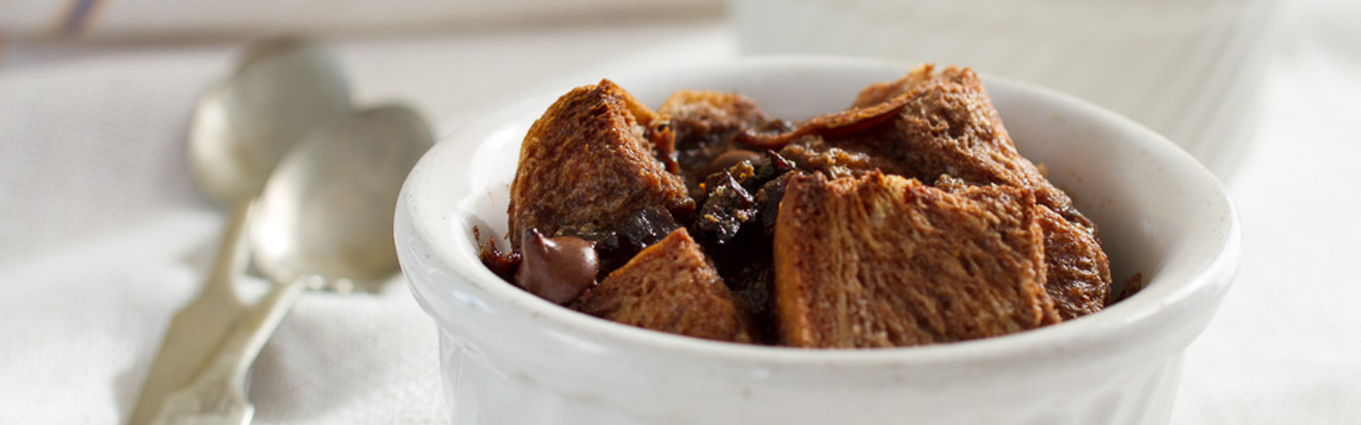 <p>Studded with prunes and chocolate and gently flavored with orange zest, this bread pudding stands out from similar recipes. Serve it alone or with crème fraîche.</p>
