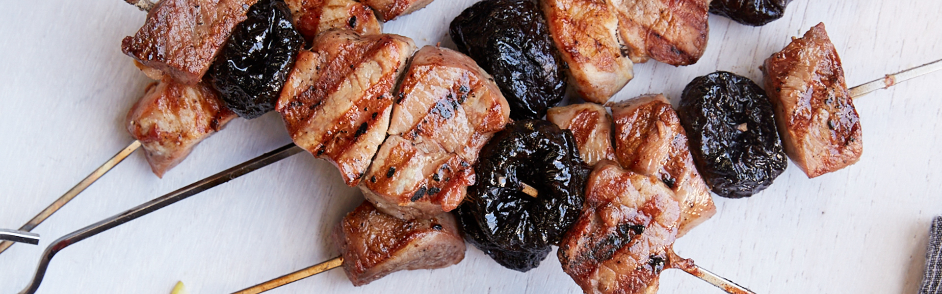 <p>When skewered between cubes of pork loin and grilled as Italian-style kebabs, prunes become addictively caramelized. Complementing the pork and prunes is a simple sauce made of walnuts, garlic, and dried cherries. Served with arugula, the dish is nutty, tangy, and naturally sweet answer to backyard barbecues.</p>