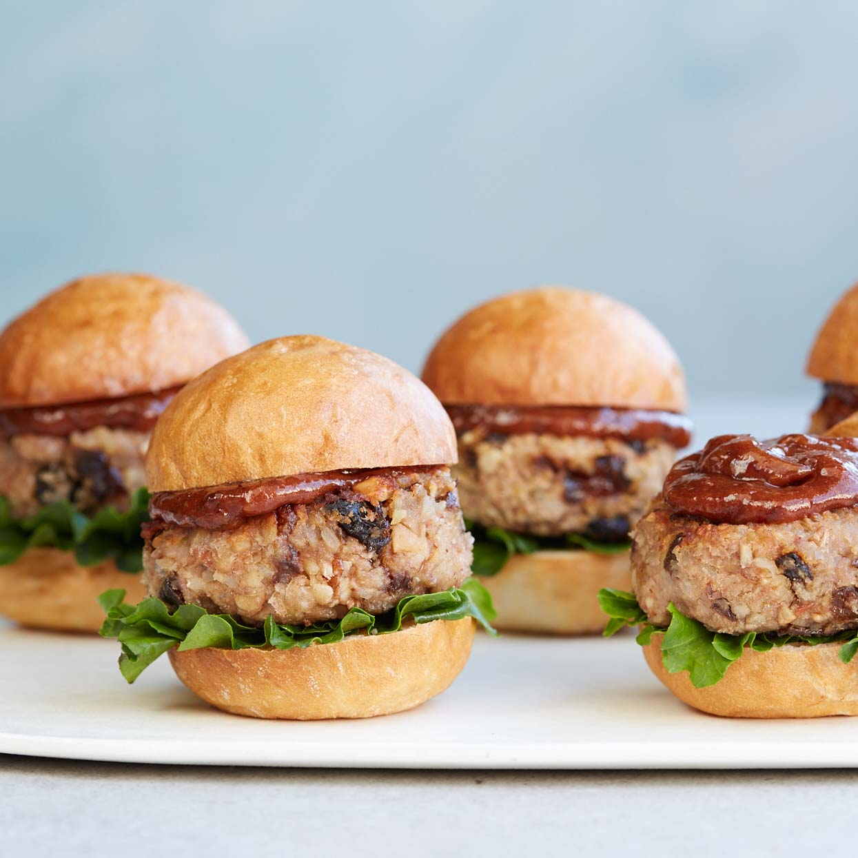 <p>A crowd-pleasing recipe for vegetarians, these sliders are packed with beans, rice, and nuts. Binding them together is a combination of prunes, egg, and panko breadcrumbs. For a tangy finish, make plum ketchup to serve with it.</p>
