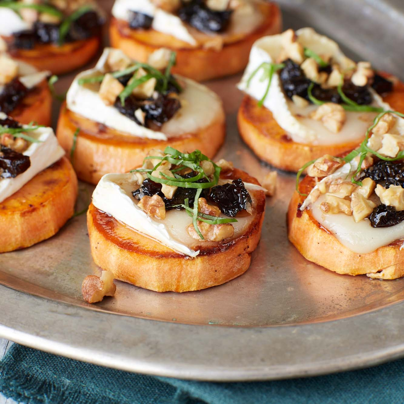 <p>With the sweet potatoes taking the place of bread, this simple but decadent recipe is the gluten-free answer to classic crostini. Seasoning prunes with a little vinegar gives the crostini a sweet-savory background.</p>