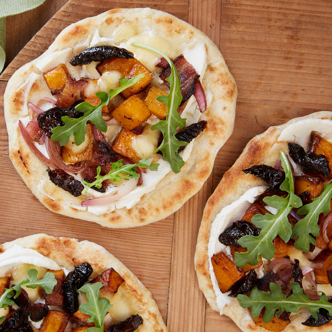 <p>Roasted butternut squash, ricotta, and bacon makes memorable mini pizzas. Topping the baked dough with arugula and prunes gives this flatbread a bright finish.</p>