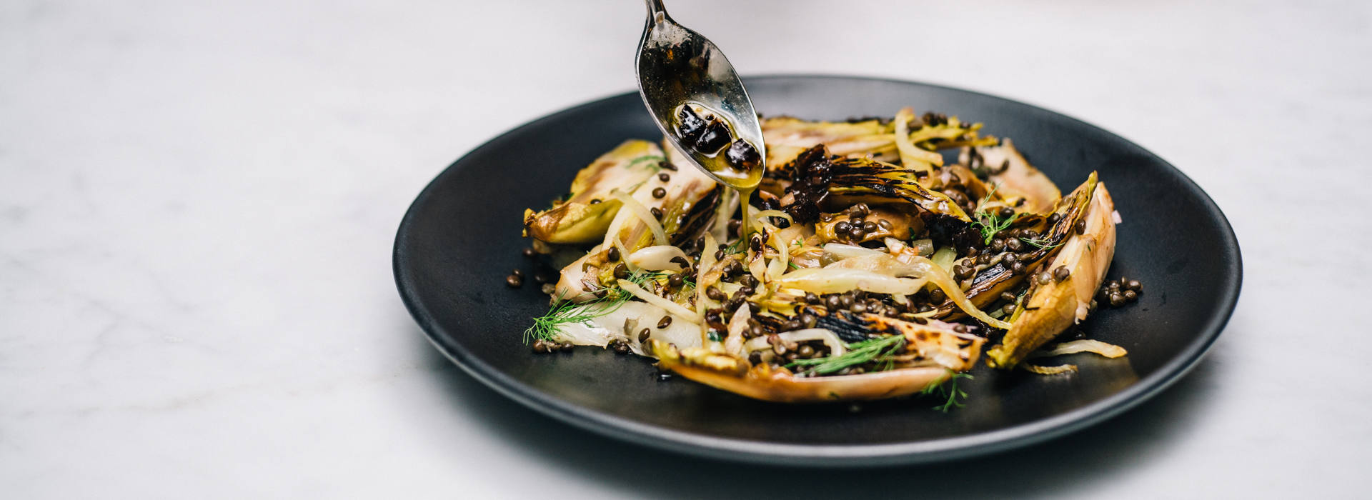 <p>Charred endive and fennel take on a deeper, sweeter flavor in this salad mixed with lentils and diced prunes and seasoned with a shallot vinaigrette. </p>